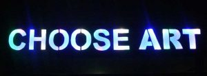 The Choose ART sign at night.